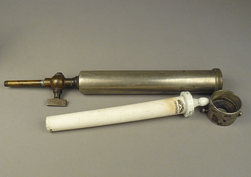 White ceramic filter tube with nipple on one end and metal pipe-like case for the ceramic filter.