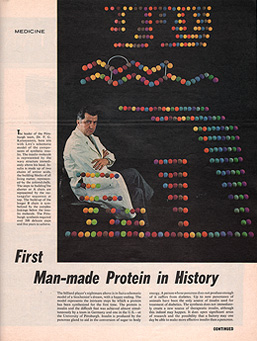 Seated man in a white lab coat with a diagram of the structure of insulin made out of colored spheres superimposed on a black background.