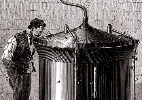 A man stands next to a large cylindrical beer vat and gazes into the vat through a small opening in the conical cover.