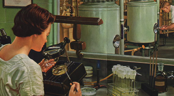 A woman seated at a laboratory bench examines a petri dish under a magnifying glass.  In the background a man examines an industrial fermentation tank.