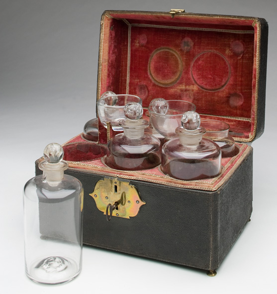 Medicine chest, containing glass bottles, a set of scales, and a mortar and pestle
