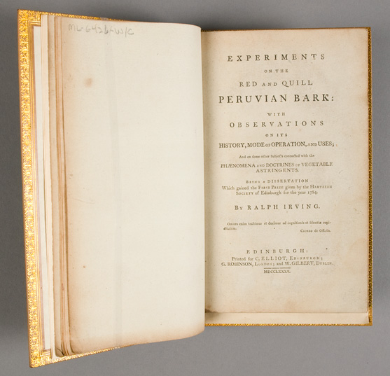 A leather bound book ornamented with gold leaf open to the title page.