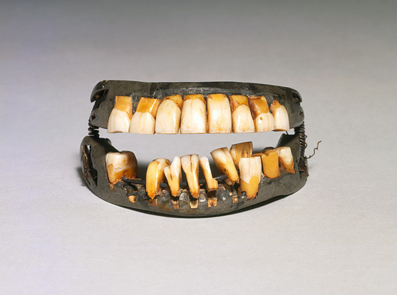 The contents of a dental hygiene kit–a weathered, brown, leather toothbrush case, and a silver, metal toothbrush, tongue scraper, and container for tooth powder–lie in an orderly arrangement.