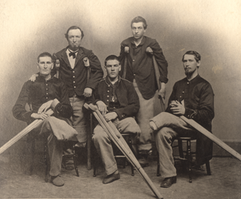 Black and white photograph of five men, each with an amputated leg, dressed in Civil War-era military uniform and holding wooden crutches.