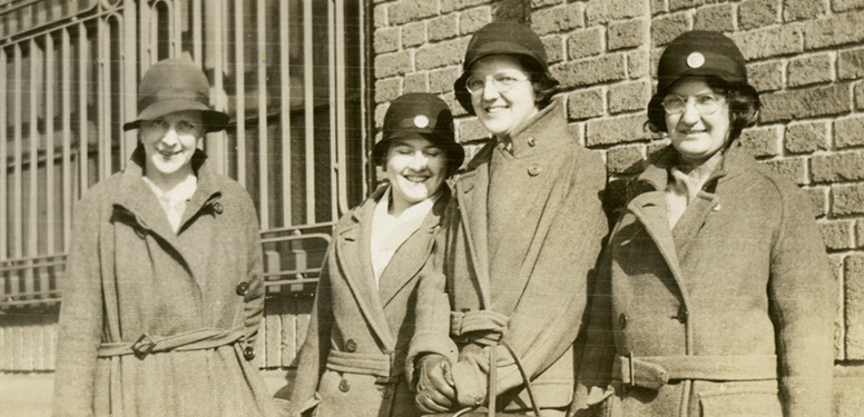 Four White female nurses in overcoats and cloche hats holding leather nursing bags and standing next to a brick building.