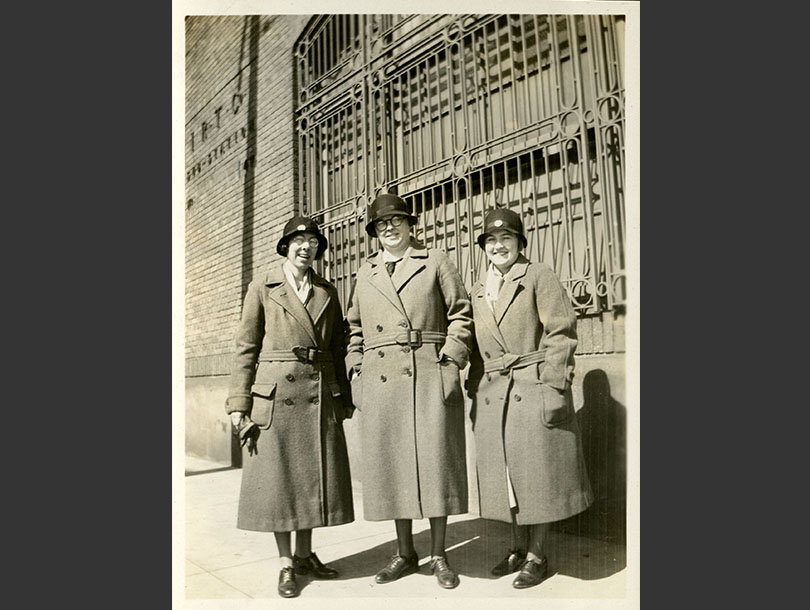 Three White female nurses in overcoats and cloche hats standing next to a brick building.