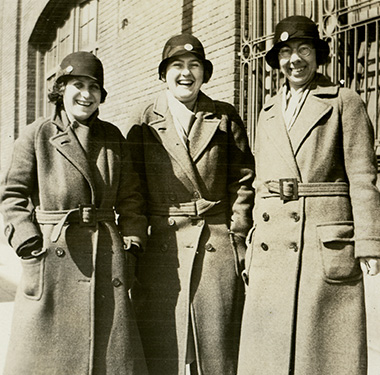 Three smiling White female nurses in overcoats and cloche hats beside a brick building.