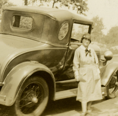 White female nurse in uniform standing beside a Ford car on a rural road.