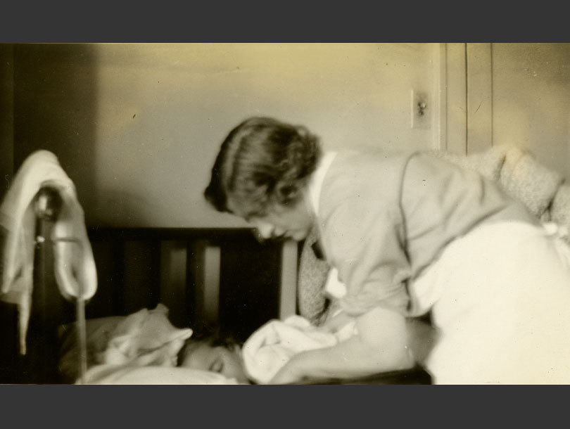 A uniformed, White, female nurse tending to a child in a crib.