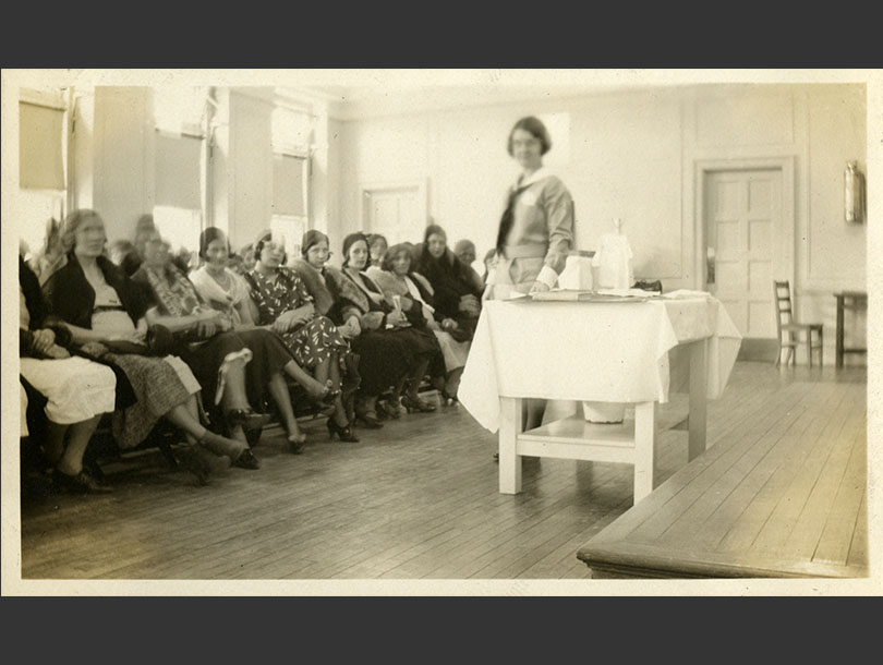 A uniformed, White, female nurse standing next to a table with an audience of seated women in front of her.
