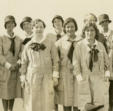 10 White females, 8 in nurse uniforms with cuffs and collars, neck ties, and 2 in dress suits.