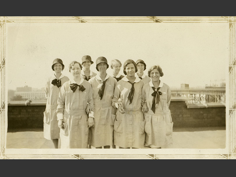 8 White female nurses in uniforms with neck ties, standing in a group.