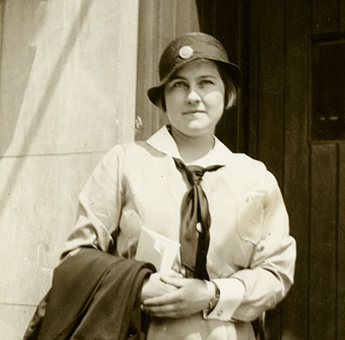 White, female nurse in cloche hat standing in a doorway, overcoat over arm.