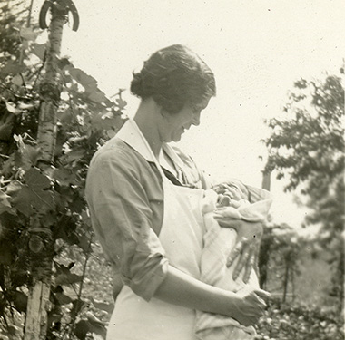 White, female nurse in a white apron holding a swaddled infant in a garden.