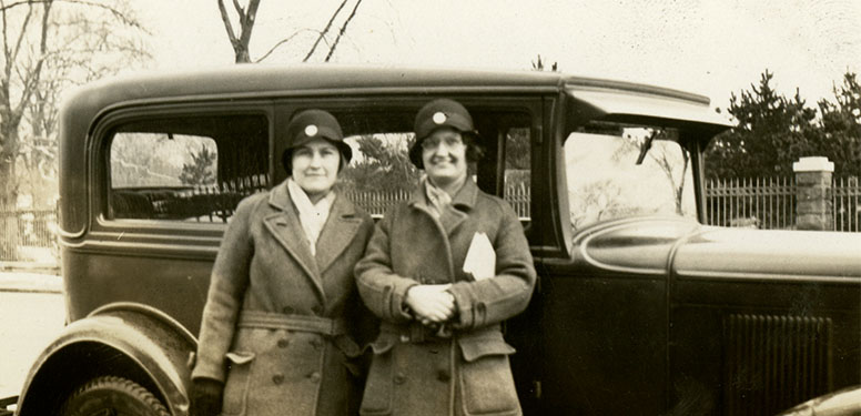 Two White female nurses in matching winter overcoats and cloche hats standing next to a Ford Victoria.