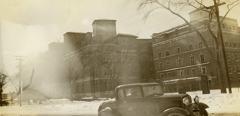 Five-story brick hospital with a Ford Model A parked along snowy road in the foreground.
