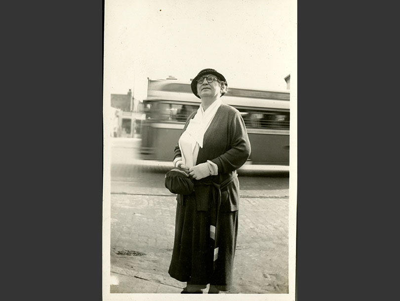 Middle-age White woman wearing a hat, glasses, and gloves, standing on a street with a bus passing behind her.