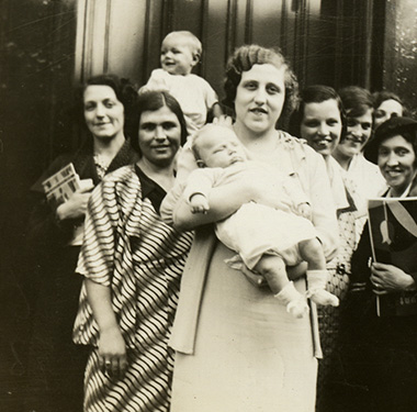 Fourteen women posing as a group, one holding a baby and one with a child in front.