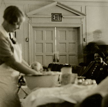 White female nurse bathing an infant in a basin while mothers observe.