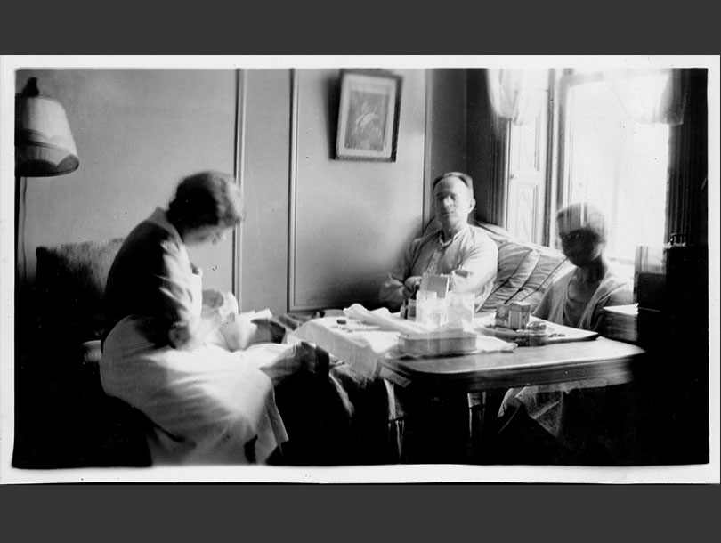 Female nurse doing a male patient's dressing while sitting next to a table with medical supplies.