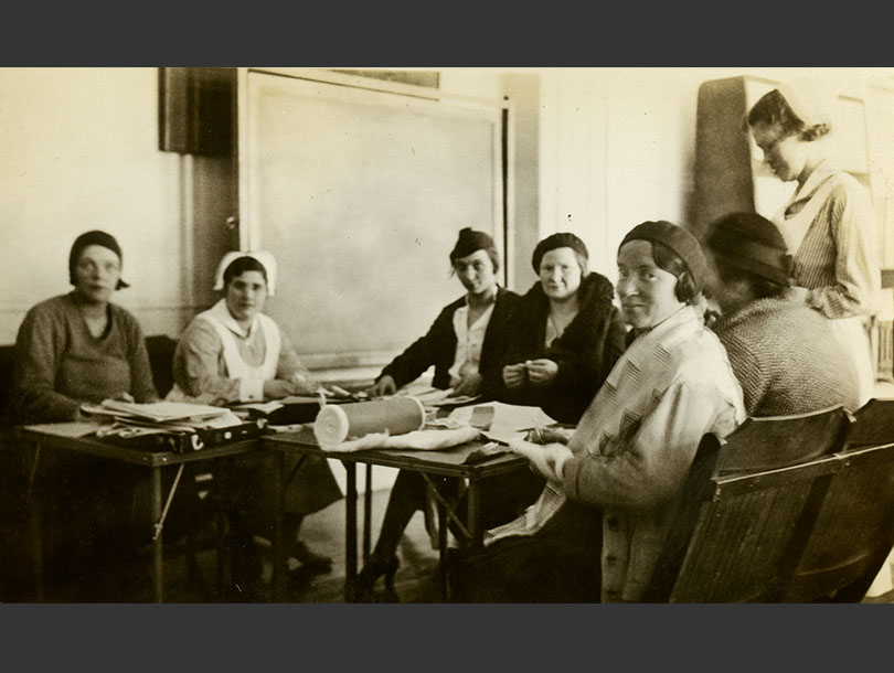 Five mothers seated around a table with supplies and two White female nurses helping with project.