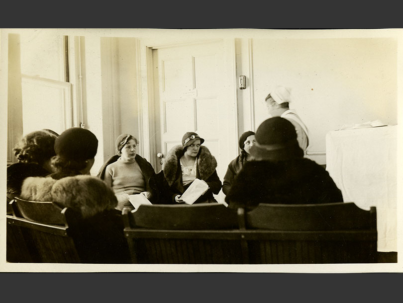 Sitting in a semi-circle, 7 females in coats watch a White female nurse in uniform conducting class.