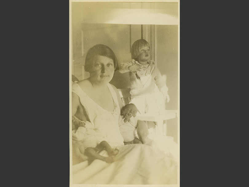 Female sitting in bed holding her newborn twins while her toddler daughter is standing nearby.