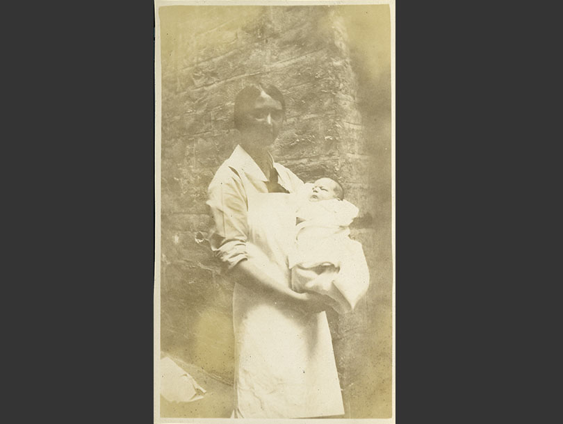 White female nurse in white apron holding an infant outside.