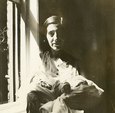 Female sitting by a window holding her twin infants.