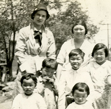 White, female nurse with a Chinese-American family comprised of a mother and seven children.