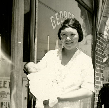 A woman holding an infant in front of a store, small child in the foreground.