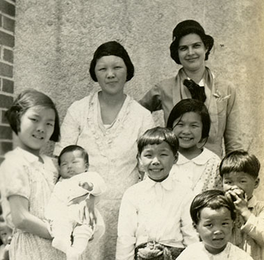 White female nurse in uniform posing with a Chinese mother and six of her children outside a laundry.