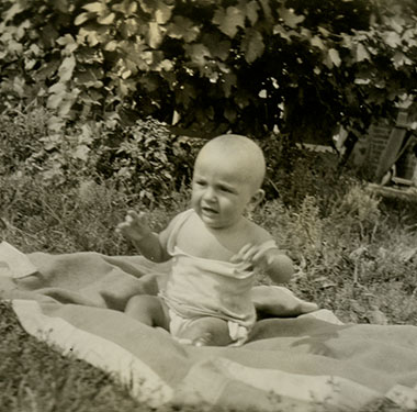 A White baby sitting up on a blanket in a grassy spot in the sun.