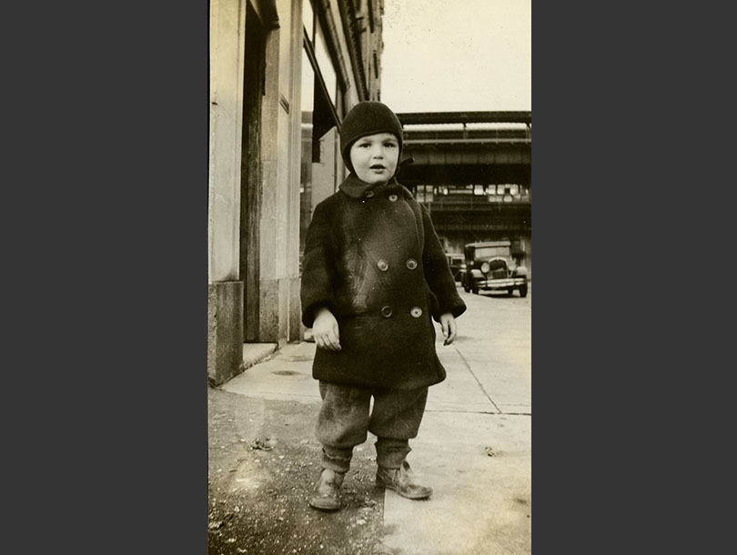 White toddler boy in winter coat and hat standing on a Bronx Street, elevated train line in background.