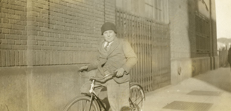 Boy posing with his bicycle on a sidewalk outside a brick building in Gun Hill.
