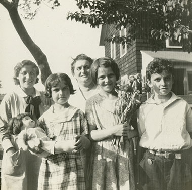 White nurse in uniform with a mother, two girls and one boy, under a tree outside a shingled home.