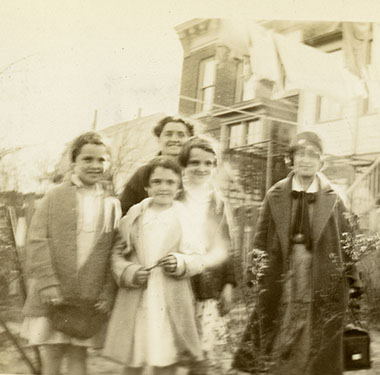 White female nurse in uniform standing with a mother, two girls, and a boy outside a walk-up home.