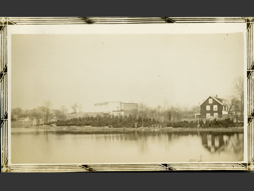 Pond with three-story shingled home and warehouse building in background.