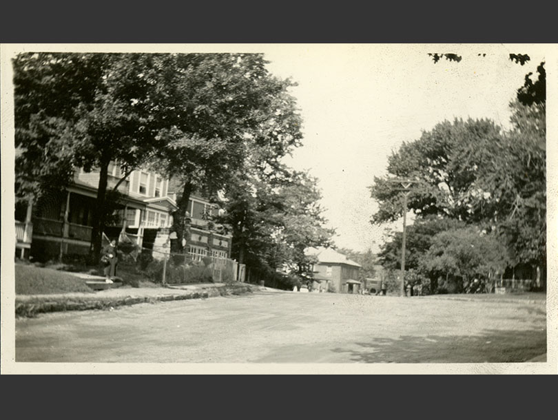 Nurse standing at bottom walkway of a house on a curving road with trees and other houses.