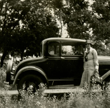 White female nurse in uniform standing beside a Ford Model A Coupe on a rural road with trees.