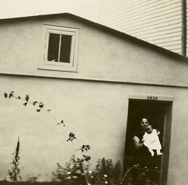 A woman holding a baby stands in the doorway of a one-story stucco or cement home.