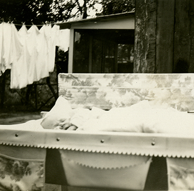 Swaddled infant rests on a wash table in a backyard, laundry hanging in the background.