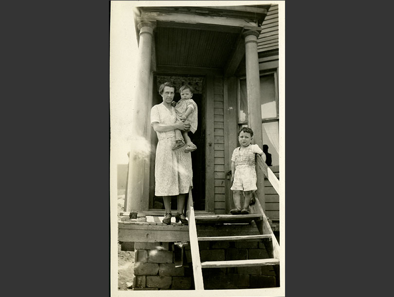A mother, holding a toddler, and a young boy stand at the top step of wooden frame house.