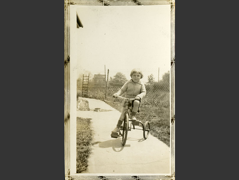 Toddler boy in sweater and shorts riding a tricycle on a cement walkway.