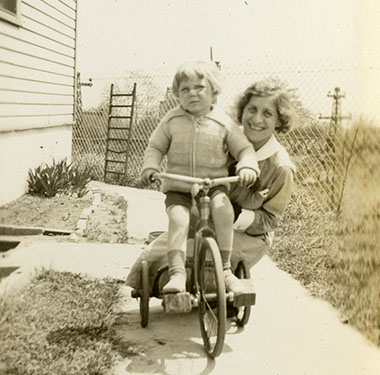 Toddler boy posing on his tricycle on a walkway, with a White nurse in her uniform kneeling behind.