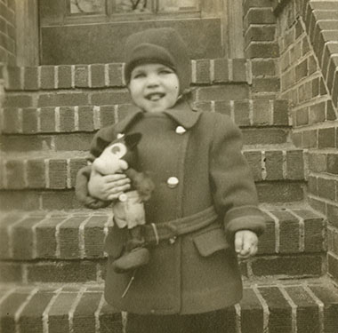 Holding a toy, a toddler boy in coat and hat stands on brick front steps.