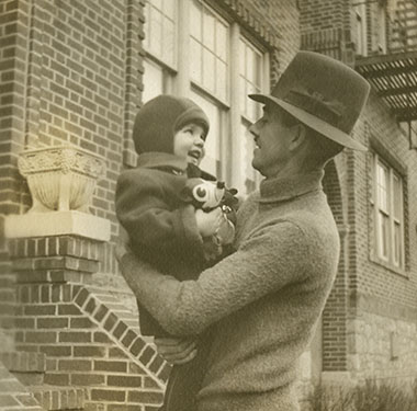 Next to brick steps, a father in hat holds his toddler son, who has a toy in his hands.