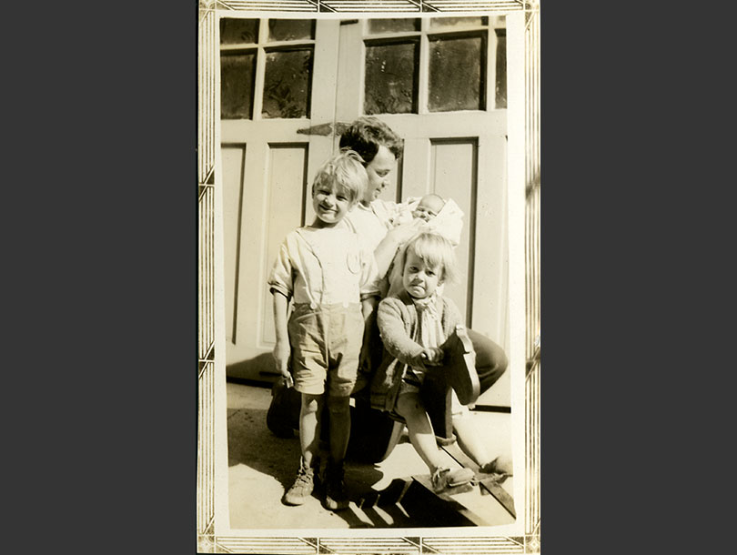 Kneeling father holding a baby, children in front of him, one standing, the other on a rocking horse.