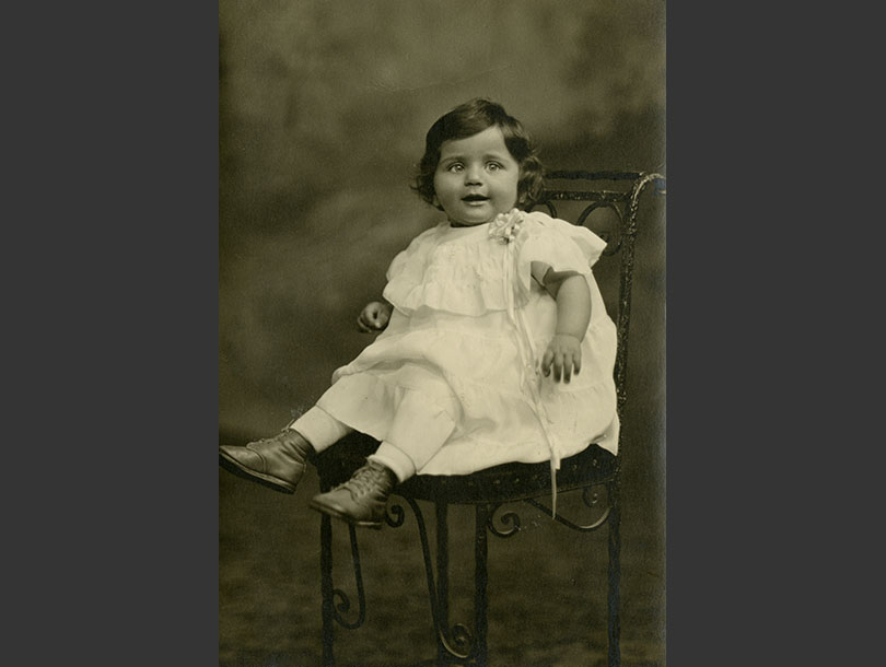 One-year-old girl in a dress sitting on a metal scrollwork chair.