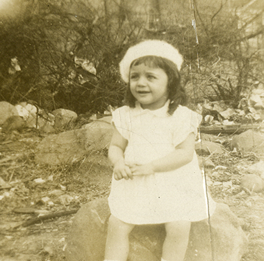 Toddler girl, wearing a dress and beret, sitting on a rock.